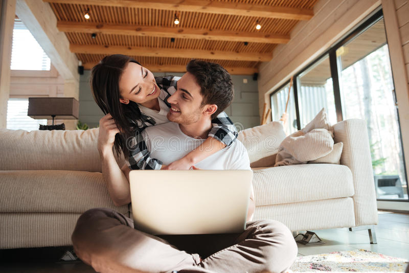 Hombre con el abrazo del ordenador portátil su mujer imagen de archivo libre de regalías