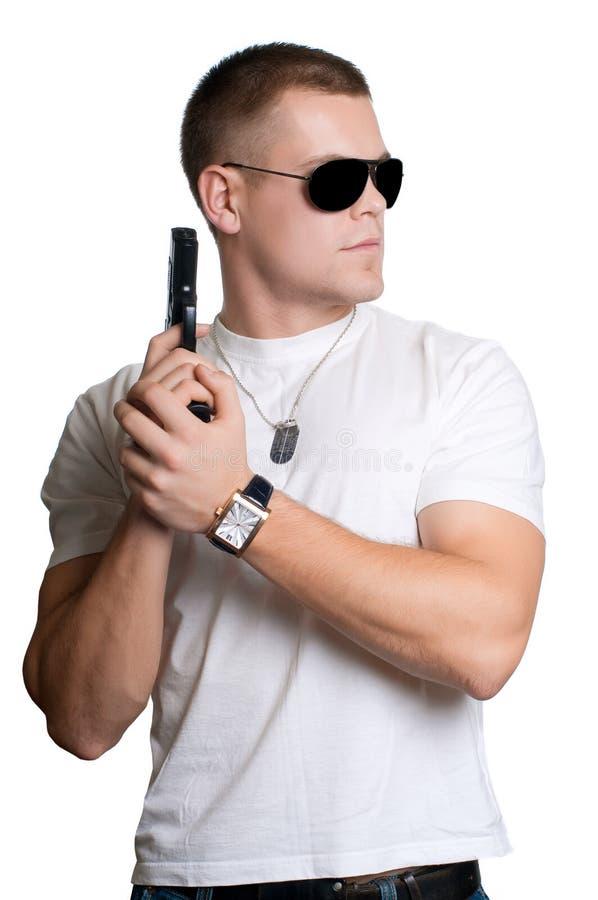 Hombre con el arma en las gafas de sol aisladas foto de archivo