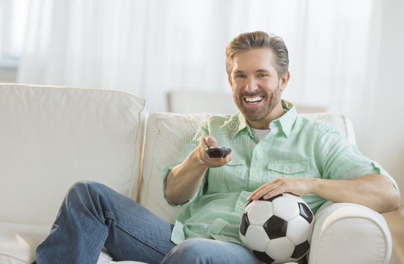 Hombre con el balón de fútbol que ve la TV fotos de archivo
