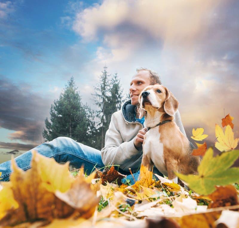 Hombre con el beagle en paisaje de la opinión del otoño foto de archivo