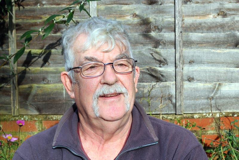 Hombre con el bigote y las lentes que llevan. imagenes de archivo