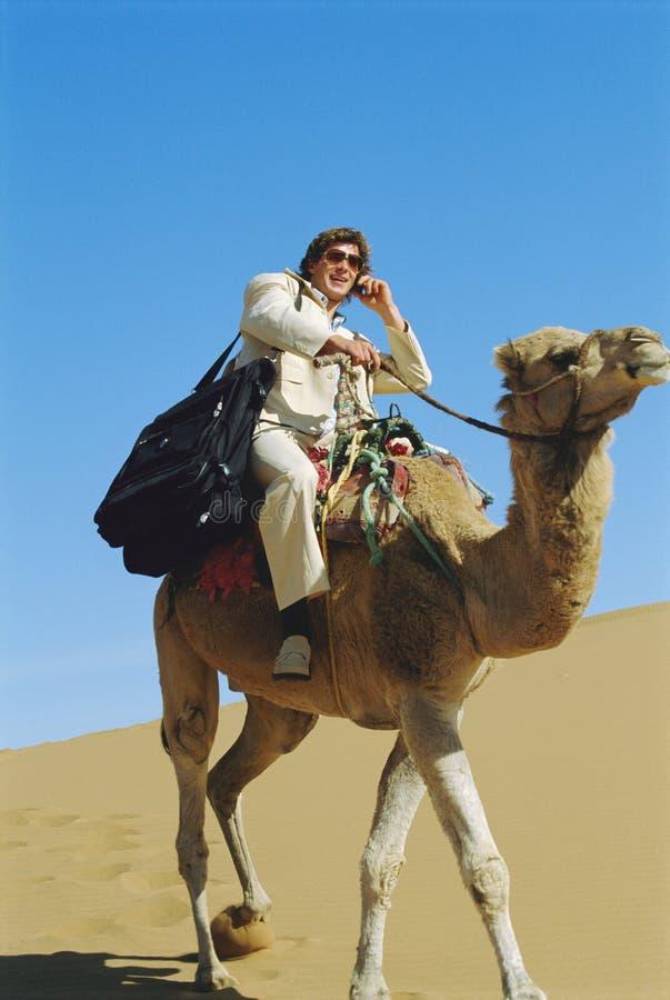 Hombre con el camello del montar a caballo del teléfono móvil en desierto foto de archivo