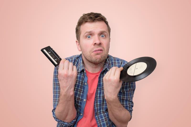 Hombre con el casete de cinta y el vinilo retro viejo confundidos y desconcertados imagen de archivo libre de regalías