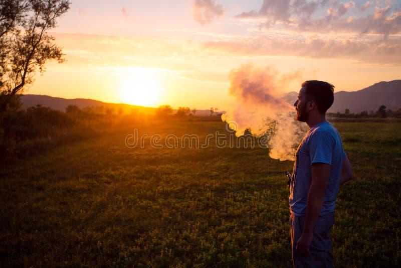 Hombre con el cigarrillo electrónico del humo de la barba al aire libre Humo del cigarrillo electrónico foto de archivo libre de regalías