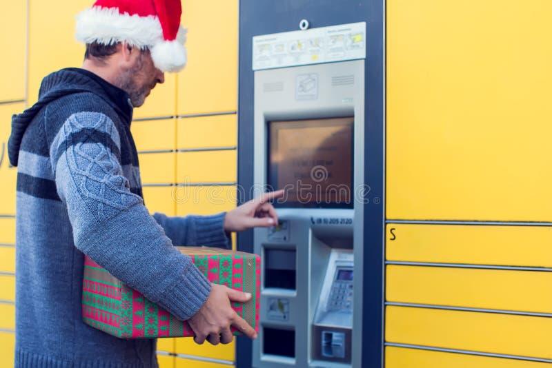Hombre con el cliente del sombrero de la Navidad que usa los posts automatizados del servicio del uno mismo imagen de archivo