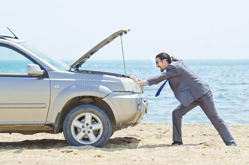 Hombre con el coche en la playa imagenes de archivo