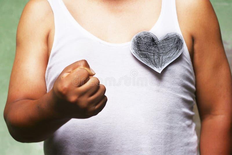 Hombre con el corazón negro que muestra el puño imagen de archivo libre de regalías