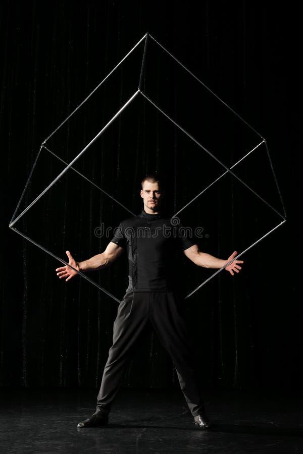 Hombre con el cubo en el fondo negro imagenes de archivo