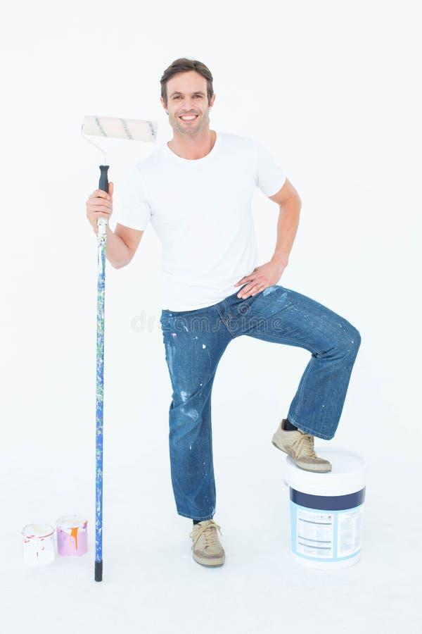 Hombre con el cubo y el rodillo de la pintura en el fondo blanco fotografía de archivo