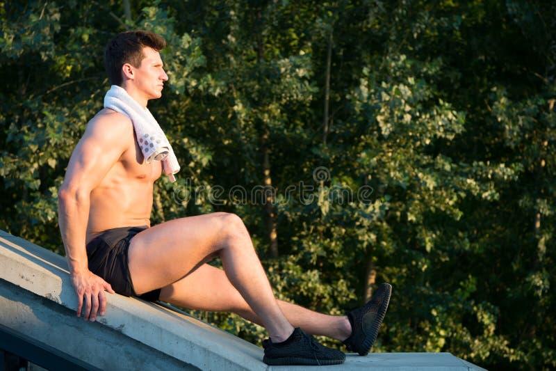 Hombre con el cuerpo atlético y toalla que se sienta en superficie concreta fotografía de archivo libre de regalías