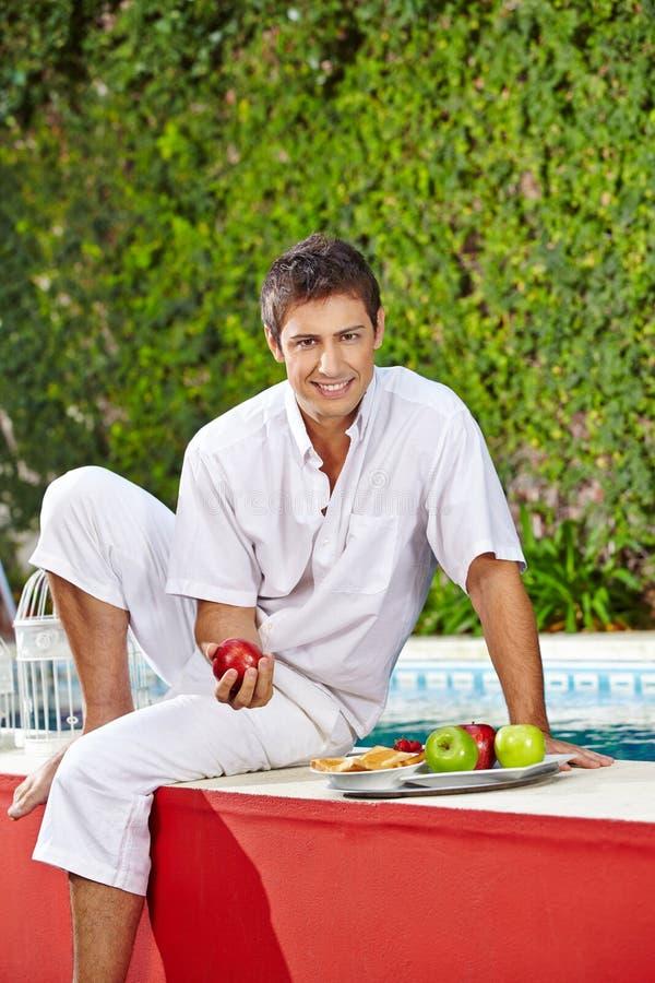 Hombre con el desayuno en la piscina del hotel foto de archivo libre de regalías