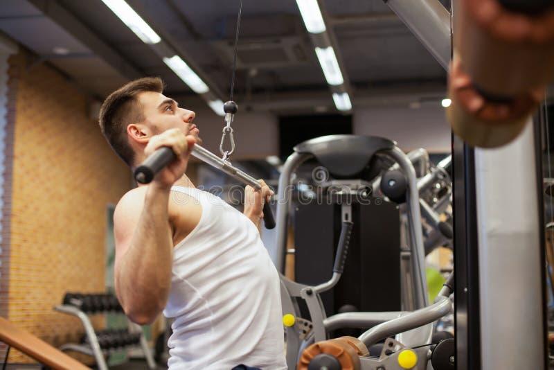 Hombre con el entrenamiento del peso en club de deporte del equipo del gimnasio imagen de archivo