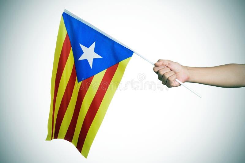 Hombre con el Estelada, la bandera catalana de la favorable-independencia, vignet fotos de archivo