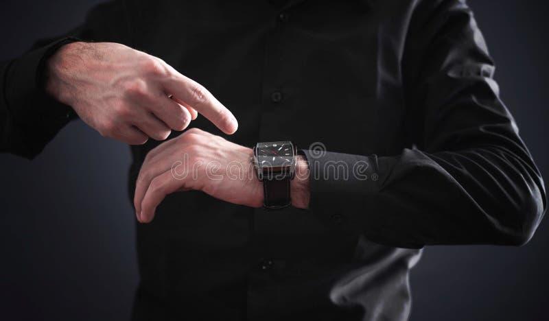 Hombre con el finger que señala su reloj imagen de archivo libre de regalías