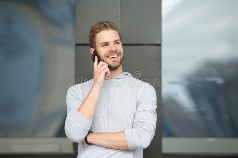 Hombre con el fondo urbano del smartphone de la llamada de la barba Smartphone feliz del uso de la sonrisa del individuo para com fotografía de archivo libre de regalías
