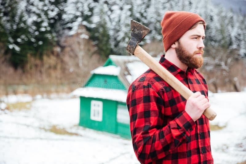 Hombre con el hacha que camina en pueblo foto de archivo libre de regalías