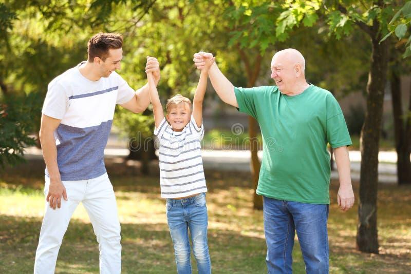 Hombre con el hijo y el padre mayor en parque fotos de archivo