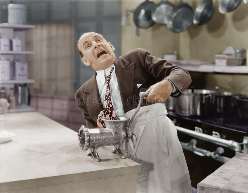 Hombre con el lazo pegado en máquina para picar carne imagenes de archivo