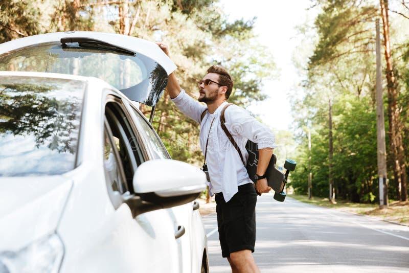 Hombre con el monopatín al aire libre que coloca el coche cercano fotografía de archivo