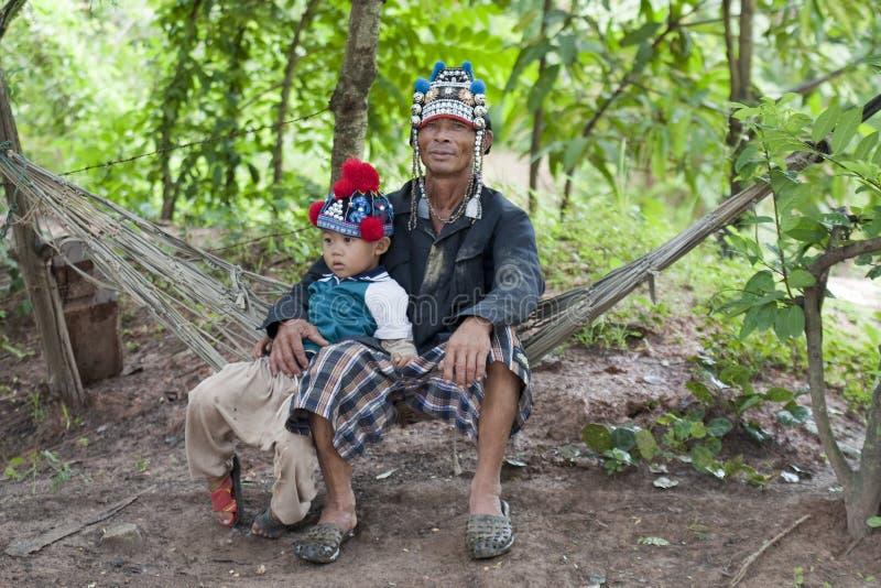Hombre con el niño de Asia en la hamaca, Akha foto de archivo