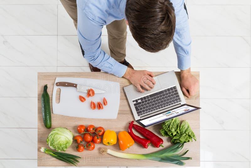 Hombre con el ordenador portátil en cocina imagen de archivo