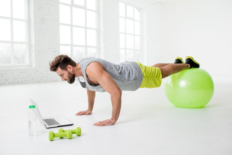 Hombre con el ordenador portátil en el gimnasio imagenes de archivo