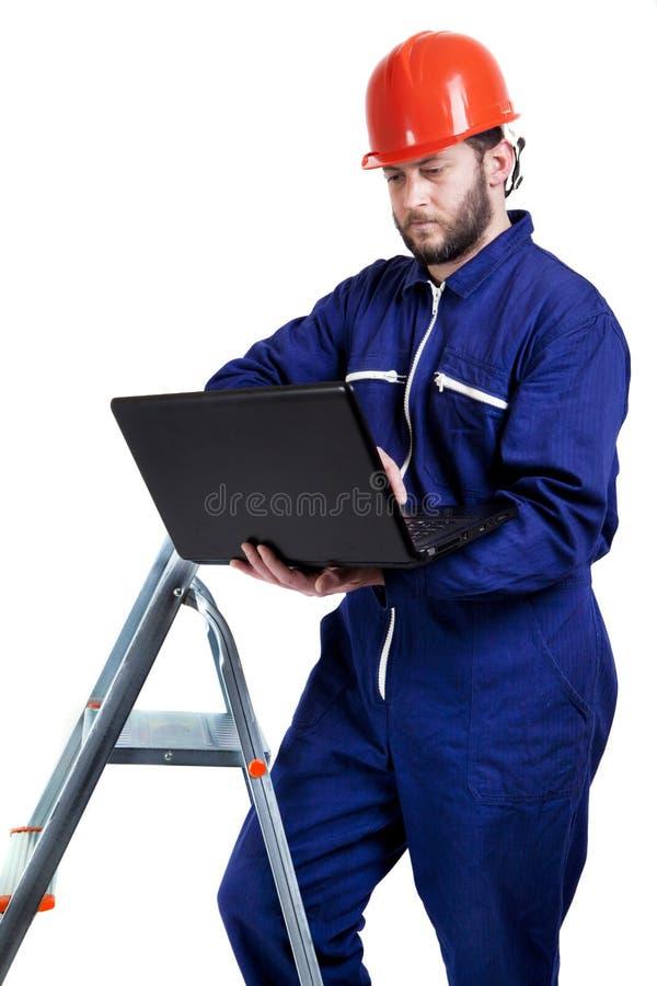 Hombre con el ordenador portátil en workwear fotografía de archivo