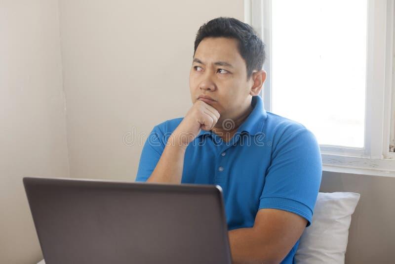 Hombre con el ordenador portátil, expresión de pensamiento fotografía de archivo libre de regalías