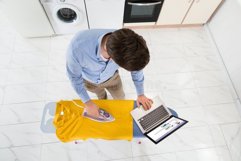 Hombre con el ordenador portátil mientras que plancha la camiseta fotografía de archivo