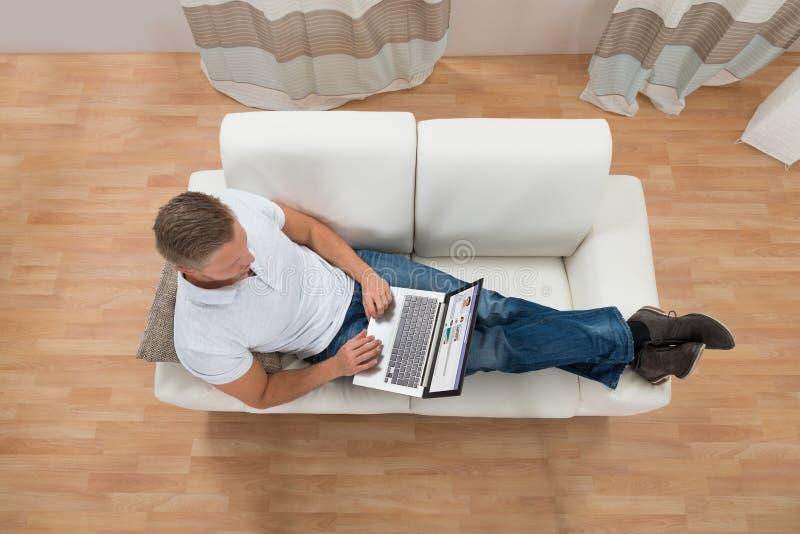 Hombre con el ordenador portátil que charla en sitio web social imagen de archivo