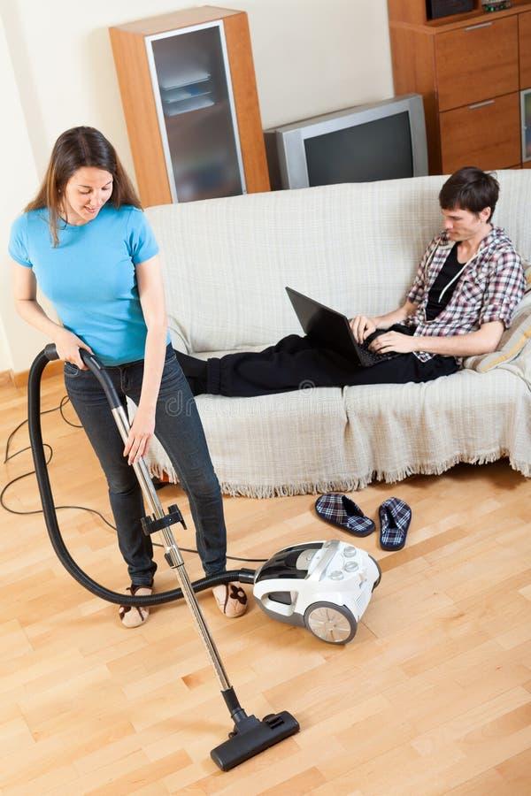 Hombre con el ordenador portátil que descansa sobre el sofá mientras que muchacha que hace la casa limpia imagenes de archivo