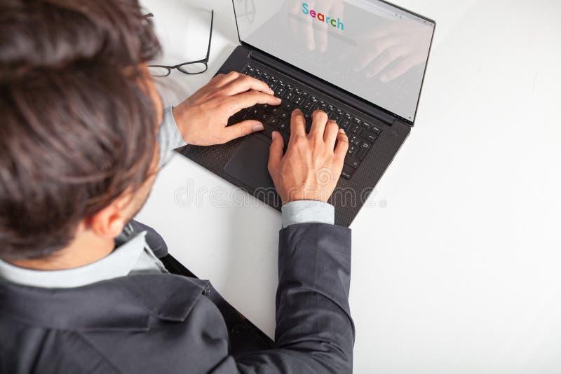 Hombre con el ordenador portátil que mecanografía en el teclado que hace una búsqueda con un Search Engine fotos de archivo