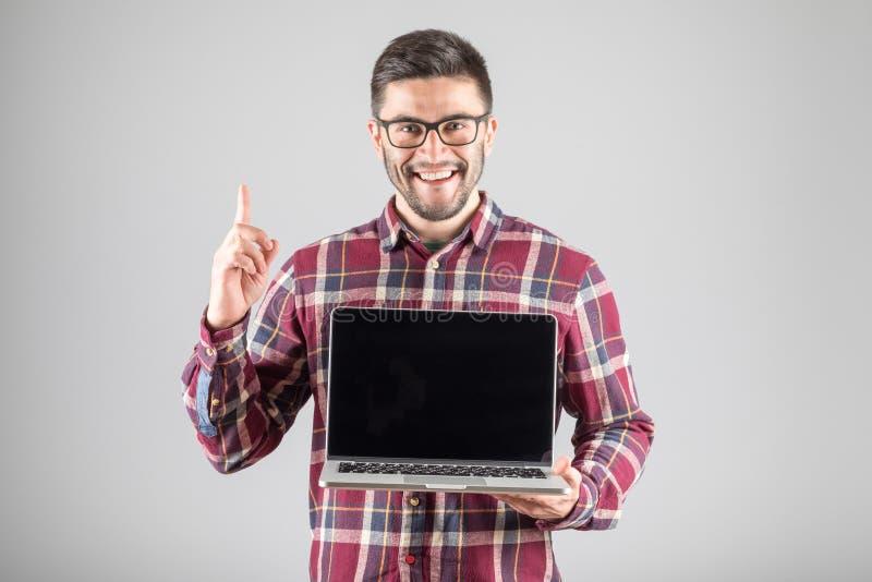 Hombre con el ordenador portátil que muestra gesto de la atención fotos de archivo