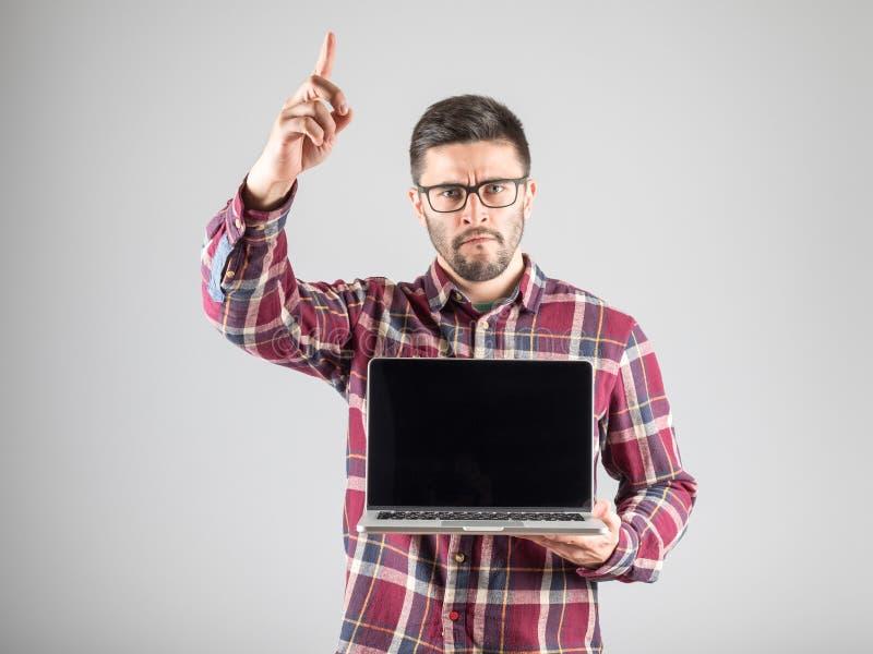Hombre con el ordenador portátil que muestra gesto de la atención imagen de archivo