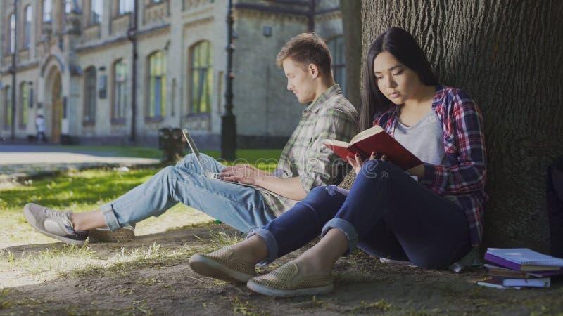 Hombre con el ordenador portátil que se sienta debajo de árbol cerca del libro de lectura de la muchacha, juventud contemporánea imagenes de archivo