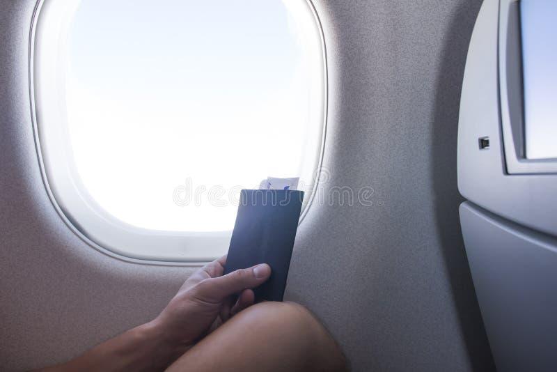 Hombre con el pasaporte y boleto que se sienta al lado de ventana en viaje de las vacaciones del aeroplano de la cabina de avione foto de archivo libre de regalías