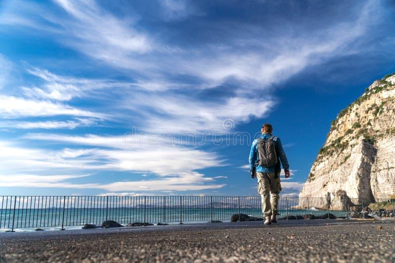 Hombre con el paseo de la mochila solo y que mira en el bacground fuerte de las ondas, de las nubes y de las montañas del agua, S fotos de archivo