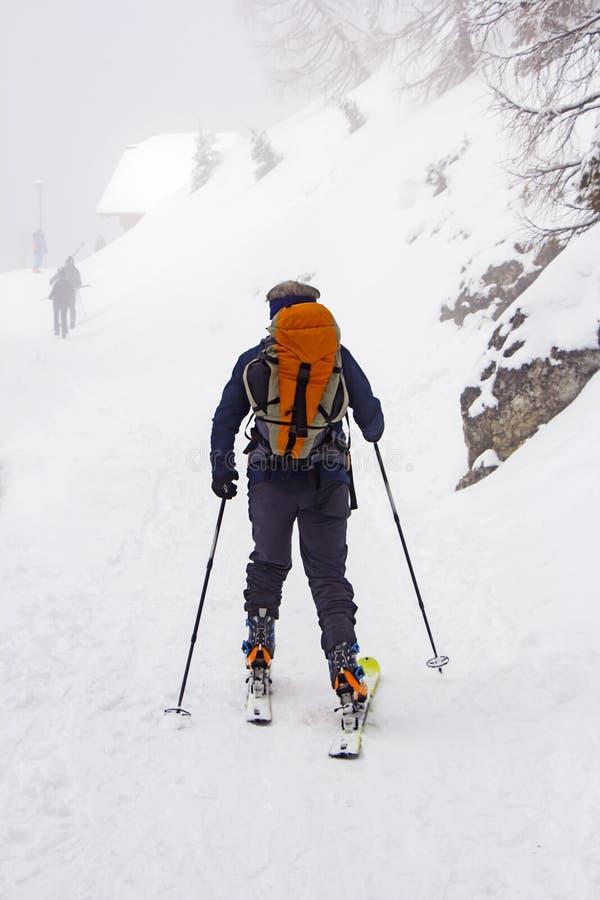 Hombre con el paseo de los esquís por la nieve foto de archivo libre de regalías