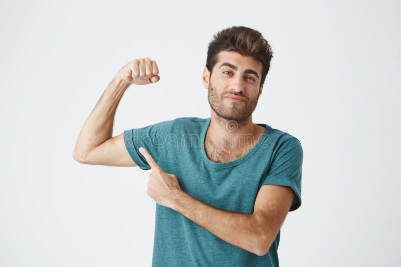 Hombre con el peinado elegante y barba que fruncen el ceño su ceja, demostrando cómo es fuerte él es Individuo apto que señala co fotografía de archivo