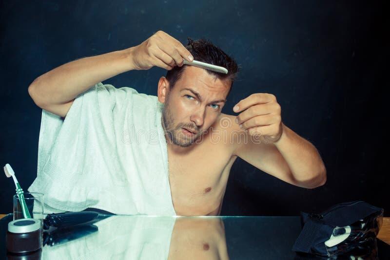 Hombre con el peine referido sobre pérdida de pelo imagenes de archivo