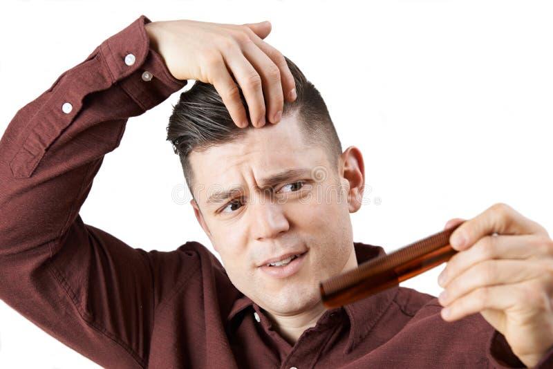 Hombre con el peine referido sobre pérdida de pelo fotos de archivo libres de regalías