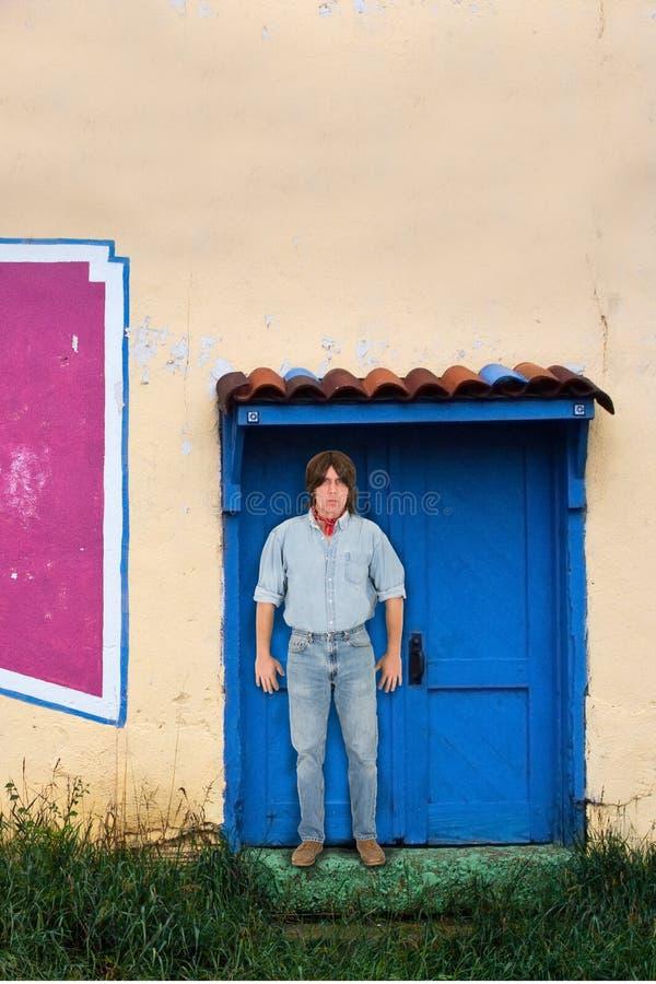 Hombre con el pelo largo que coloca el umbral del edificio de Adobe imágenes de archivo libres de regalías