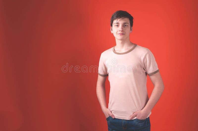 Hombre con el pelo oscuro en la situación beige de la camiseta con las manos en bolsillos en el fondo coralino imagenes de archivo
