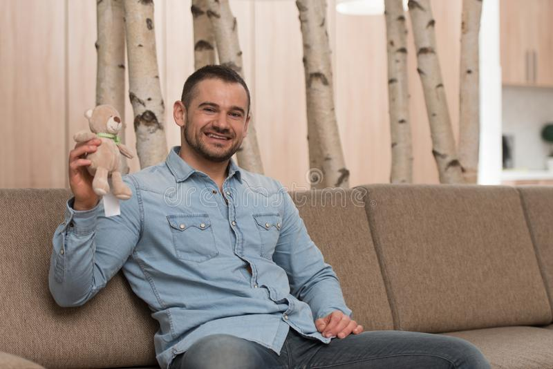 Hombre con el pequeño juguete lindo en el sofá foto de archivo libre de regalías