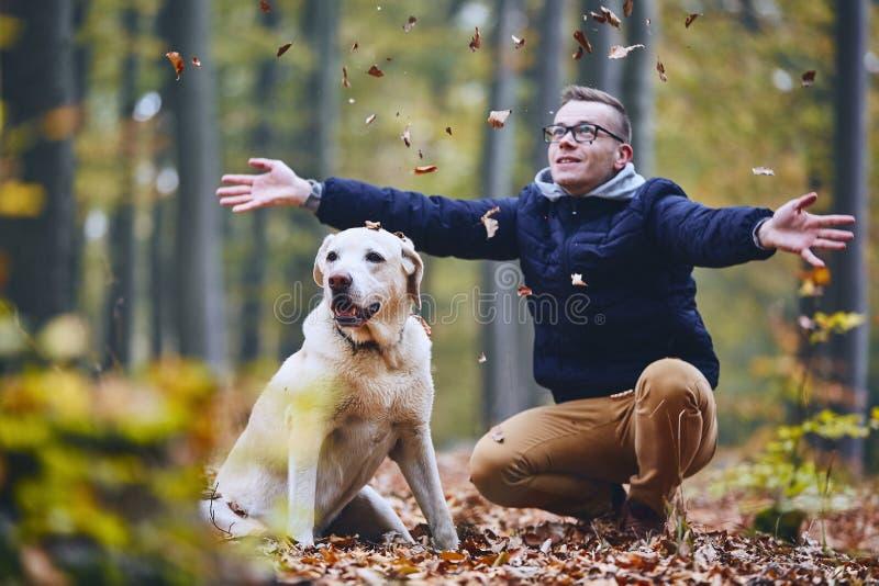 Hombre con el perro en bosque del otoño fotografía de archivo