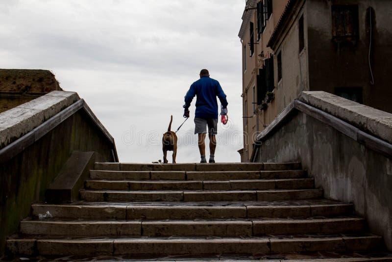 Hombre con el perro en Chioggia foto de archivo