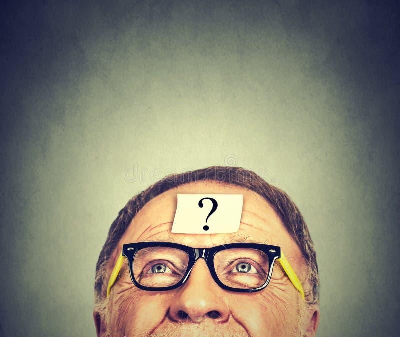 Hombre con el signo de interrogación en fondo gris de la pared foto de archivo libre de regalías