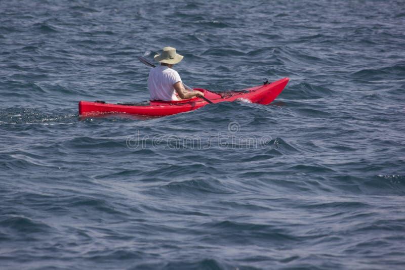 Hombre con el sombrero blanco que rema el barco rojo en un mar azul claro fotos de archivo