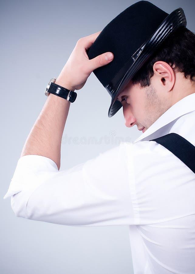 Hombre con el sombrero en fondo gris foto de archivo
