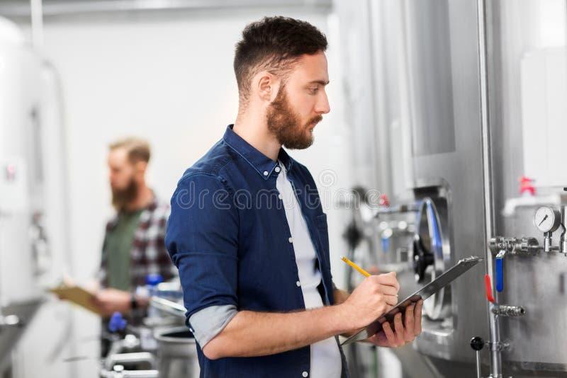 Hombre con el tablero en la cervecería del arte o la planta de la cerveza fotos de archivo